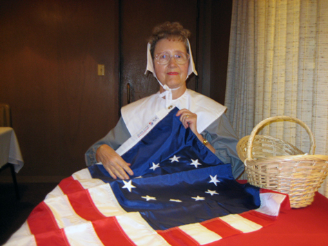 Mary Bhuta portrays Betsy Ross as the designer and seamstress of the United States flag